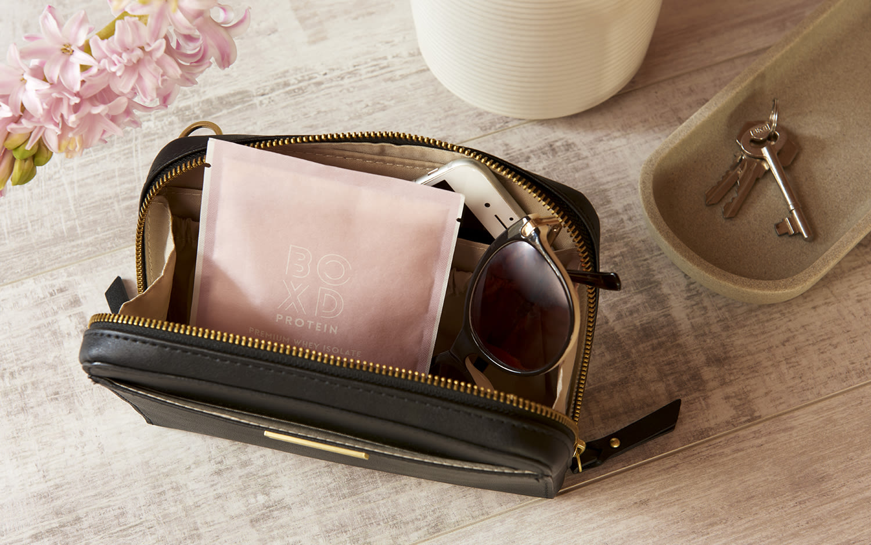 BOXD protein powder in women's bag