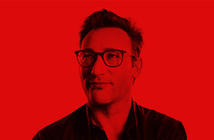 Simon Sinek in front of a red background